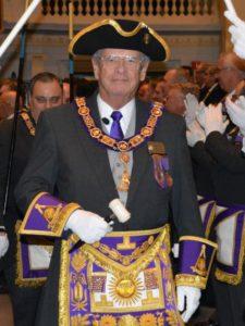 Grand Master Paul F. Gleason enters a Freemasons business meeting.